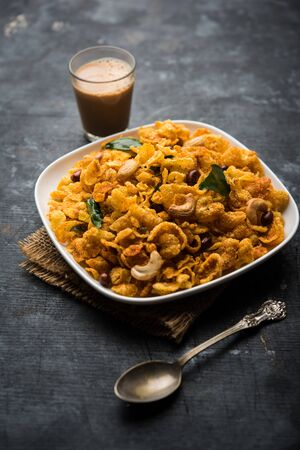 Cornflake Chivda or Corn Chiwda loaded with peanuts and Cashew. Served in a plate. selective focus