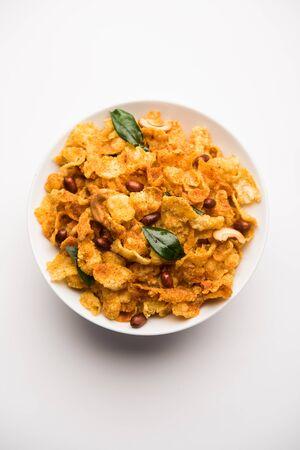 Cornflake Chivda oder Corn Chiwda mit Erdnüssen und Cashew beladen. Auf einem Teller serviert. selektiver Fokus