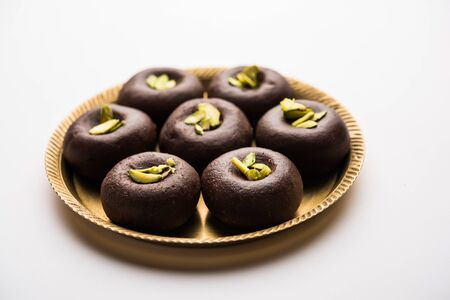 Chocolate Milk peda or pera or pedha made using sweet condensed Milk and cocoa powder, garnished with Pistachio. selective focus
