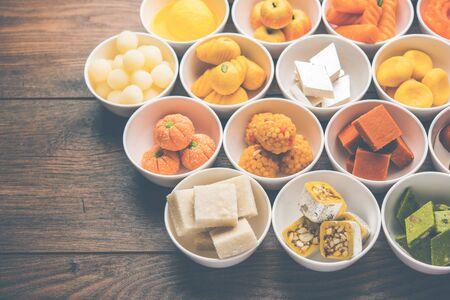Rangoli mit verschiedenen indischen Süßigkeiten/Mithai in Schüssel für Diwali oder andere Feste, selektiver Fokus