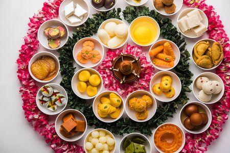 Rangoli mit verschiedenen indischen Süßigkeiten/Mithai in Schüssel für Diwali oder andere Feste, selektiver Fokus Standard-Bild