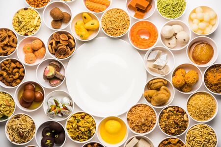 Rangoli of sweets and Farsan/snacks in bowls for Diwali with diya over white background Stock fotó