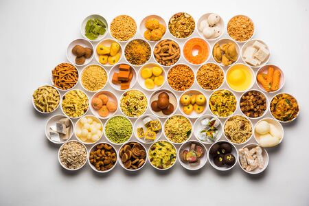 Rangoli de dulces y Farsan / bocadillos en tazones para Diwali con diya sobre fondo blanco.