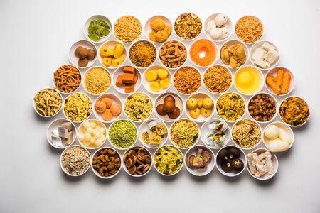 Rangoli słodyczy i Farsan/przekąski w miseczkach na Diwali z diyą na białym tle