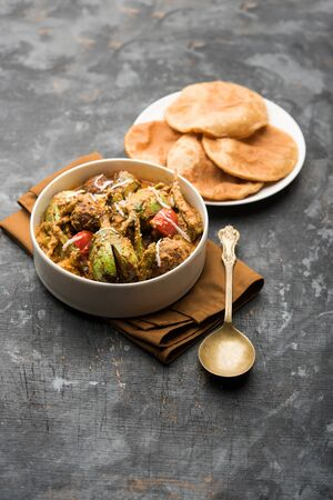 Undhiyu is a Gujarati mixed vegetable dish, specialty of Surat, India. Served in a bowl with or without poori Stock Photo - 130719095