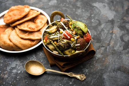 Undhiyu is a Gujarati mixed vegetable dish, specialty of Surat, India. Served in a bowl with or without poori Stock Photo - 130719013