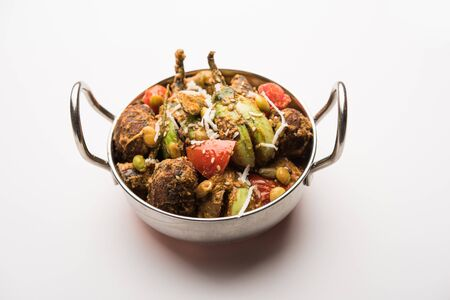 Undhiyu is a Gujarati mixed vegetable dish, specialty of Surat, India. Served in a bowl with or without poori Stock Photo - 130718624