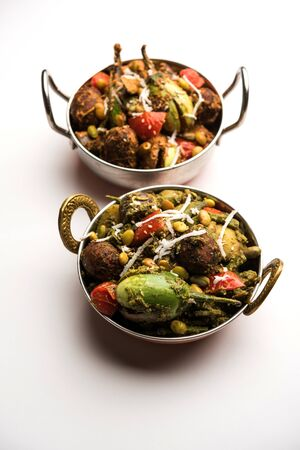 Undhiyu is a Gujarati mixed vegetable dish, specialty of Surat, India. Served in a bowl with or without poori Stock Photo - 130718633