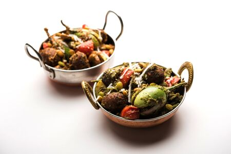 Undhiyu is a Gujarati mixed vegetable dish, specialty of Surat, India. Served in a bowl with or without poori Stock Photo - 130718634