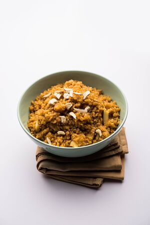 Wheat Laapsi/Lapsi/Shira/Halwa is an Indian sweet dish made of broken wheat or Daliya pieces and ghee along with nuts, raisins and dried fruits. It's a healthy food. served in a bowl, selective focus Stock Photo