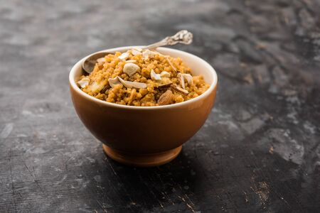 Wheat Laapsi/Lapsi/Shira/Halwa is an Indian sweet dish made of broken wheat or Daliya pieces and ghee along with nuts, raisins and dried fruits. It's a healthy food. served in a bowl, selective focus Stock fotó