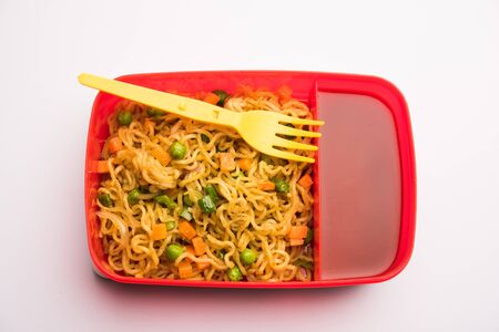 Lunch Box / Tiffin for Indian kids, contains hot noodles with fresh vegetables along with tomato ketchup.