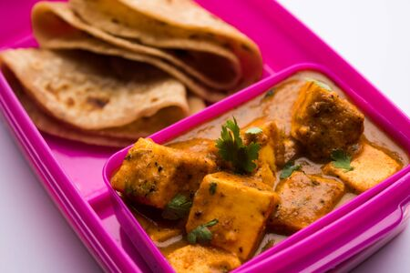 Paneer Butter Masala with Roti in lunch box or tiffin, selective focus