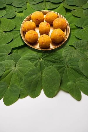 Indian Festival Dussehra, symbolic Golden or Piliostigma leaf or Bauhinia racemosa also known as Apta patti, arranged in circular pattern with Bundi or motichoor laddu served in plate at centre 写真素材
