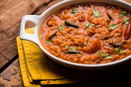 Lenticchie rosse cucinate Dal o Dhal o Masoor daal tadka servite in una ciotola, fuoco selettivo