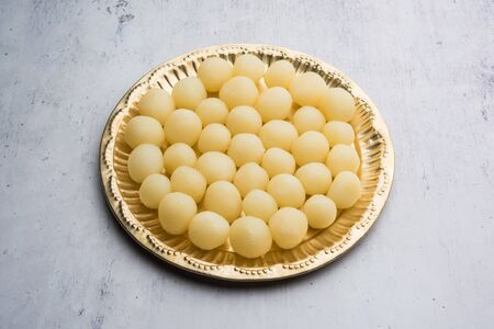 Indian Rasgulla or dry Rosogulla dessertsweet served in a golden plate. selective focus Banco de Imagens