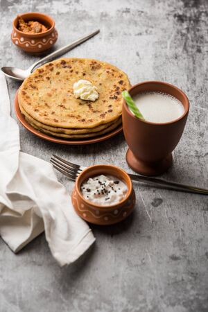 Aloo Paratha / Indian Potato stuffed Flatbread with butter on top. Served with fresh sweet Lassi, chutney and pickle . selective focus