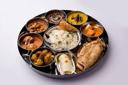 Indian vegetarian Food Thali or platter includes paneer butter masala, dal makhani / tarka, chole papad, kofta curry, gulab jamun, aloo-gobi sabji, chapati and rice with Bengali sweet served Stock Photo