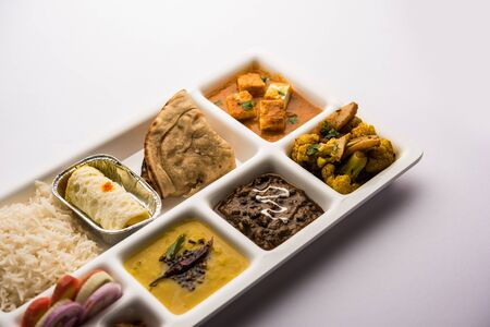 Indian vegetarian Food Thali or Parcel food-tray with compartments in which paneer, dal makhani / parka, aloo-gobi sabji, chapati and rice with Bengali sweet served