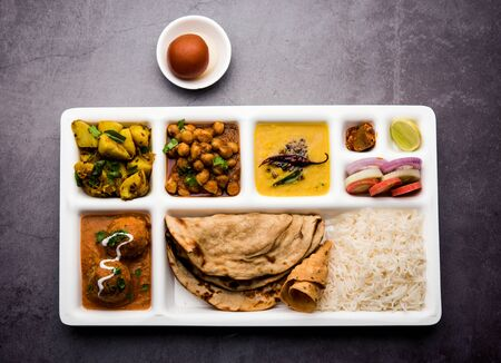 Indian vegetarian Food Thali or Parcel food-tray with compartments in which Malai Kofta, chole, Dal tarka, dry aloo sabji, chapati and rice with sweet gulab jamun served
