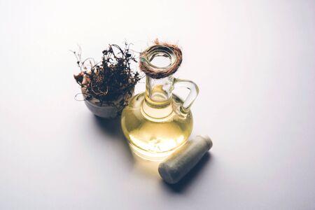 Ayurvedic Maha Bhringraj or Mahabhringraj Hair Oil with dried leaves and mortar, selective focus Stock Photo