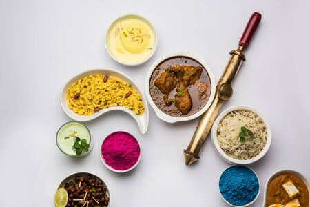 Happy Holy concept showing Indian assorted lunch food like chicken, paneer butter masala, naan, jeera rice, black chana fry, jalebi, fujiyama, thandai and Farsan with holi colours and pichkari