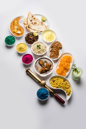 Happy Holy concept showing Indian assorted lunch food like chicken, paneer butter masala, naan, jeera rice, black chana fry, jalebi, fujiyama, thandai and Farsan with holi colours and pichkari Standard-Bild