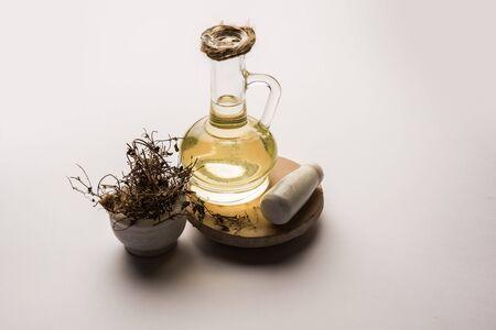 Ayurvedic Maha Bhringraj or Mahabhringraj Hair Oil with dried leaves and mortar, selective focus