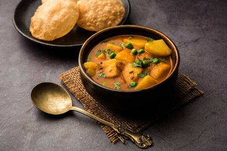 Aloo puri or potato curry with fried poori, popular Indian breakfast / lunch / dinner menu.