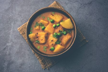Aloo curry sabzi made using boiled potato with green peas. Served in a bowl Фото со стока