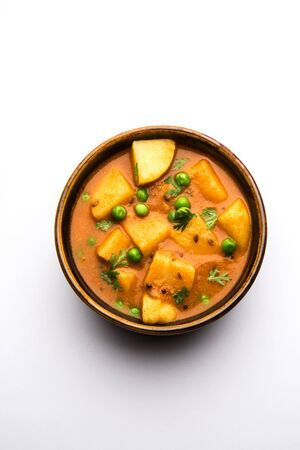 Aloo curry sabzi made using boiled potato with green peas. Served in a bowl Reklamní fotografie