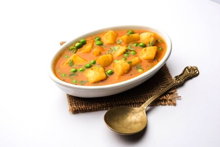 Aloo curry sabzi made using boiled potato with green peas. Served in a bowl 免版税图像