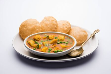 Aloo puri or potato curry with fried poori, popular Indian breakfast / lunch / dinner menu. Фото со стока