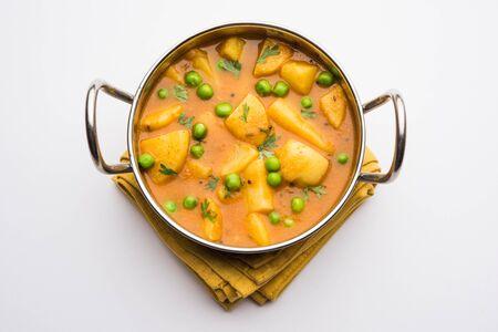 Aloo curry sabzi made using boiled potato with green peas. Served in a karahi 免版税图像