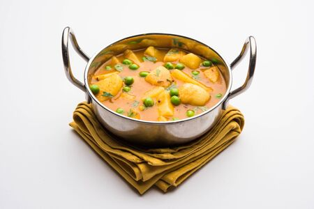 Aloo curry sabzi made using boiled potato with green peas. Served in a karahi Stock fotó