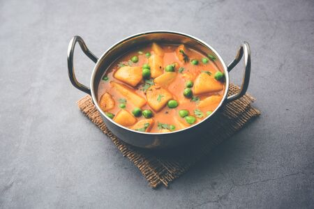 Aloo curry sabzi made using boiled potato with green peas. Served in a karahi Фото со стока