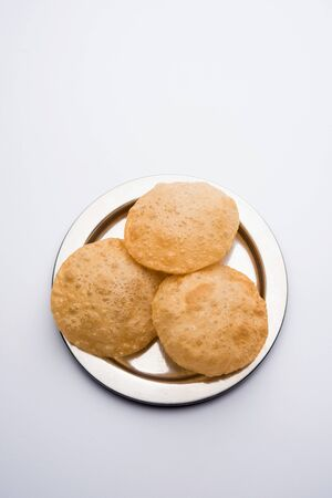 Plain puri served on a plate. It's an Indian deep-fried bread made from whole-wheat flour, popular main course or breakfast recipe