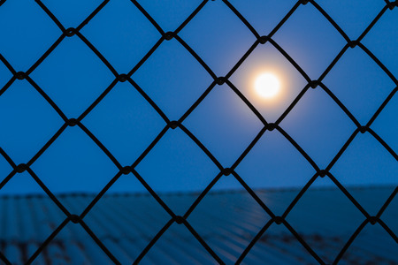 confined: Moon looked out of the shadows in prison. Stock Photo