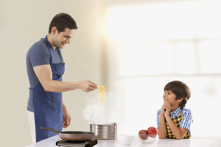 about age: Father and son preparing noodles in kitchen