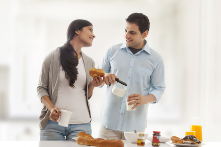 a jar stand: Young couple enjoying breakfast at kitchen table