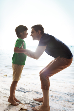 about age: Cheerful father lifting son at beach on sunny day