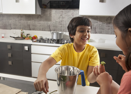 a jar stand: Two children having fun together in kitchen