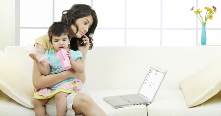 Mother holding her child while talking on the phone
