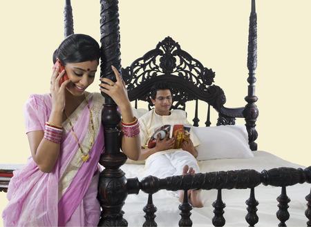 Bengali woman stitching while husband reads a magazine