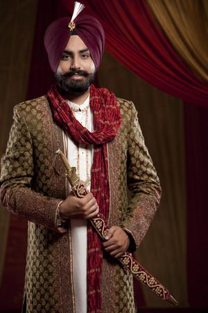 Portrait of a Sikh groom holding a sword LANG_EVOIMAGES