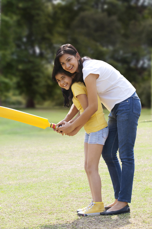 Mother and daughter playing cricket  LANG_EVOIMAGES