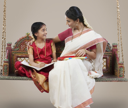 South Indian woman sitting with her daughter