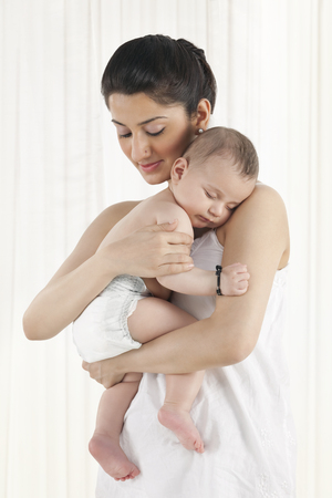 Mother holding a sleeping baby  LANG_EVOIMAGES