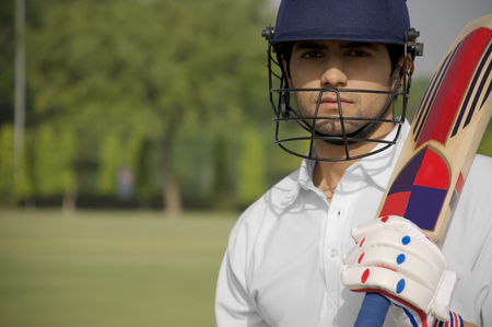 Cricketer holding a bat LANG_EVOIMAGES