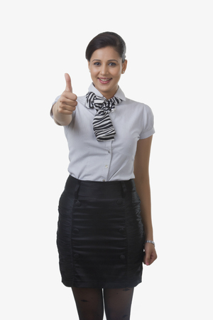 Portrait of air hostess giving thumbs up